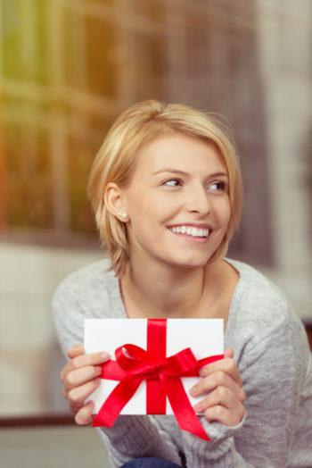 lächelnde blonde frau zeigt einen gutschein